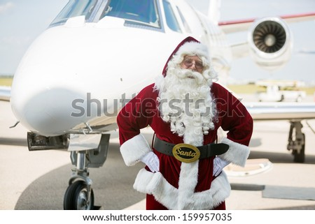 Portrait of Santa with hands on hip against private jet at airport terminal - stock photo