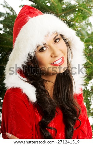 Portrait of santa woman with christmas tree on a background, looking at the camera. - stock photo