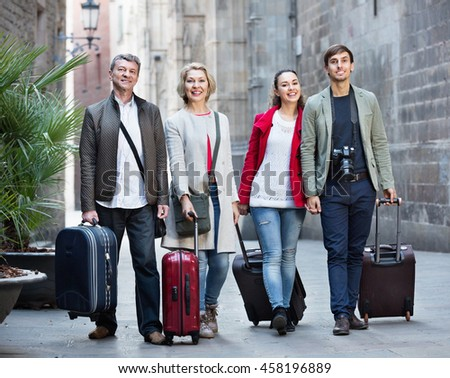 Portrait of satisfied cheerful young and mature couple with baggage outside in spring - stock photo