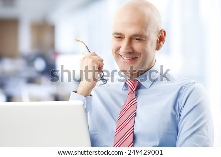 Portrait of satisfied sales man sitting in front of computer while working at office. - stock photo
