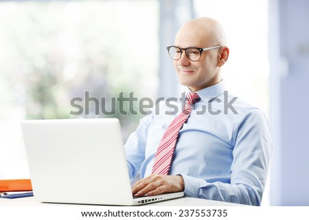 Portrait of satisfied sales man working on laptop and sitting at office.  - stock photo