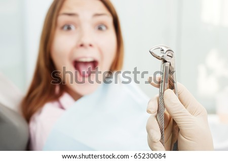 portrait of scared woman at dentist's office - stock photo