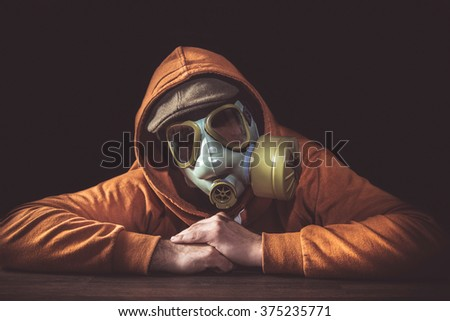 Portrait of scary man with gas mask, low key  - stock photo