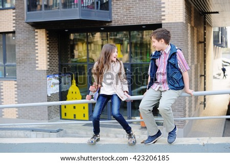 Portrait of school aged boy and girl having fun outside in the city - stock photo
