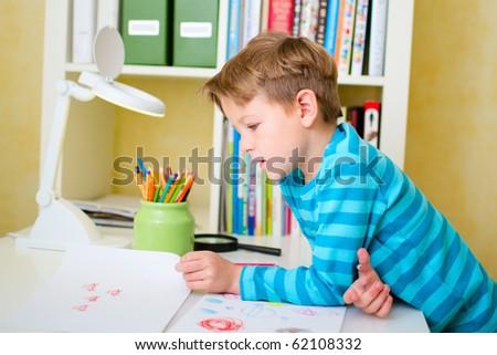 Portrait of school boy doing homework at home - stock photo