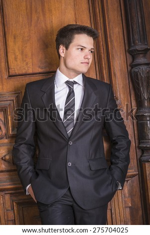 Portrait of School Boy. Dressing formally in black suit, necktie, white shirt, hands in pockets, a young handsome college student standing against vintage style office door on campus, looking away.  - stock photo