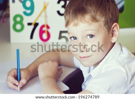 Portrait of school boy in white shirt writing in his exercise book - stock photo