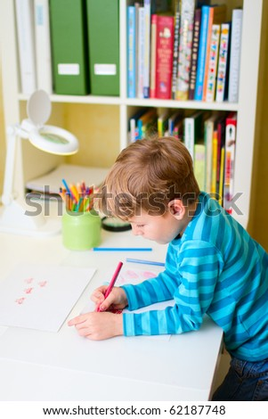 Portrait of school boy studying at home - stock photo