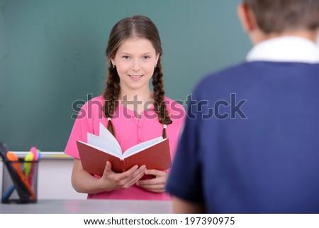 Portrait of school children, learning on blackboard background - stock photo