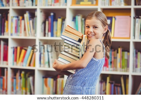 Portrait of school girl holding stack of books in library at school