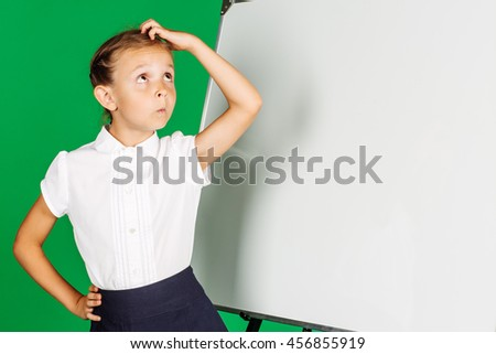 portrait of school girl in a school uniform near whiteboard with her hand scratching head . Learning, idea and school concept. Image on green background. - stock photo