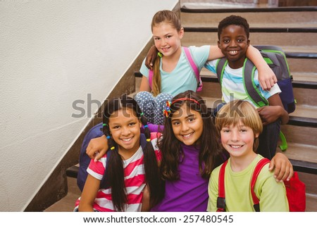 Portrait of school kids sitting on stairs in the school - stock photo