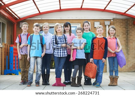 Portrait Of School Pupils Outside Classroom Carrying Bags - stock photo