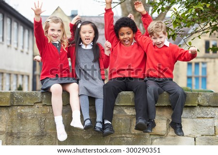 Portrait Of School Pupils Sitting On Wall Together - stock photo