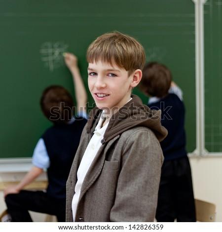 Portrait of schoolboy at blackboard background - stock photo