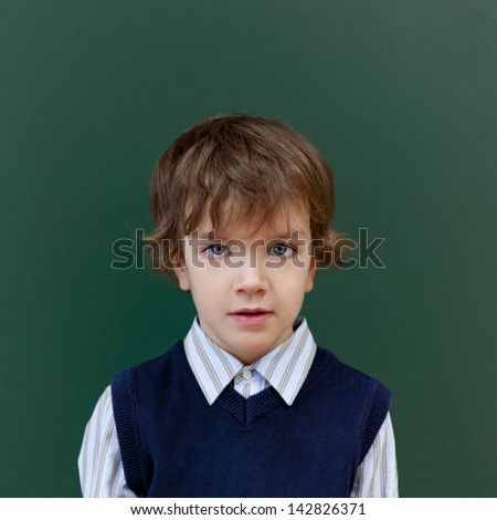 Portrait of schoolboy at blackboard background - stock photo