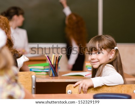 Portrait of schoolboy at workplace with teacher on background - stock photo
