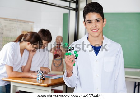 Portrait of schoolboy holding molecular structure with friends in background - stock photo