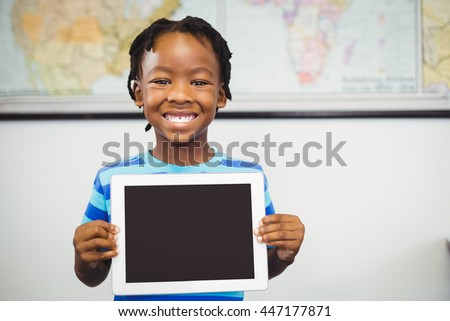 portrait of schoolboy showing digital tablet in classroom at school - stock photo