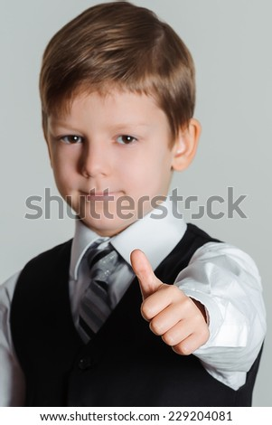 Portrait of schoolboy showing thumbs up gesture,  selective focus - stock photo
