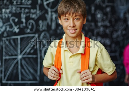 Portrait of schoolboy with blackboard on the background - stock photo
