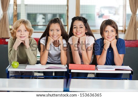 Portrait of schoolchildren leaning at desk together in classroom - stock photo