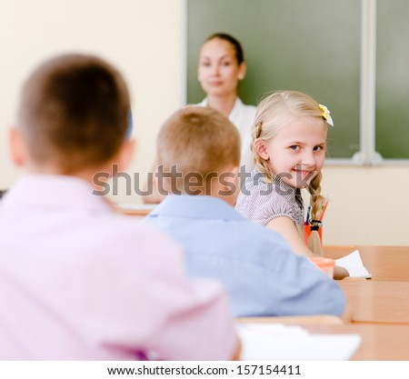 Portrait of schoolgirl at workplace with teacher on background