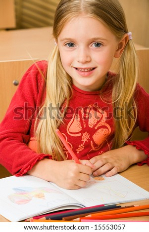 Portrait of schoolgirl drawing in her copybook during lesson and looking at camera - stock photo