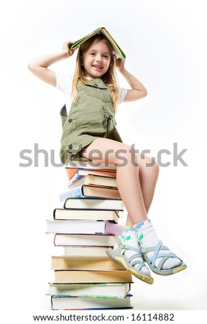 Portrait of schoolgirl holding textbook over head and sitting on the stack of books - stock photo