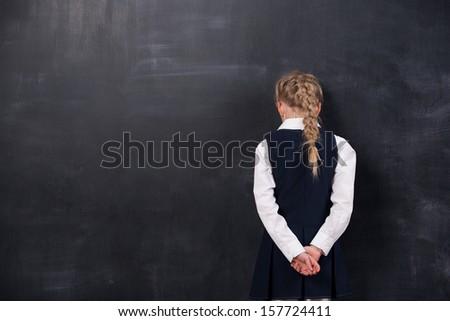 Portrait of schoolgirl leaning her forehead against blackboard - stock photo