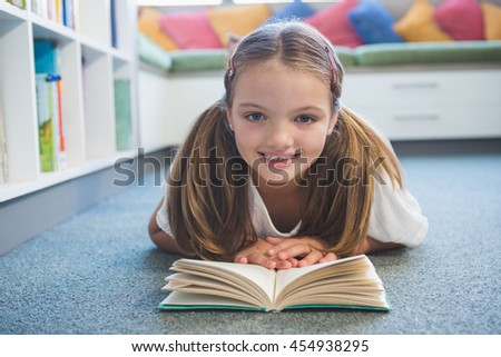 Portrait of schoolgirl lying on floor and reading a book in library at school - stock photo