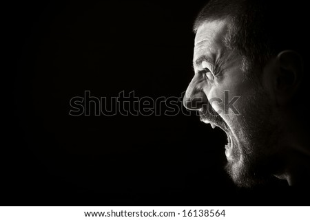 Portrait of screaming angry man on black background - stock photo