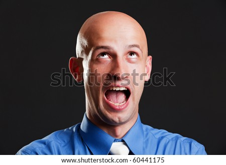 portrait of screaming bald man over black background - stock photo