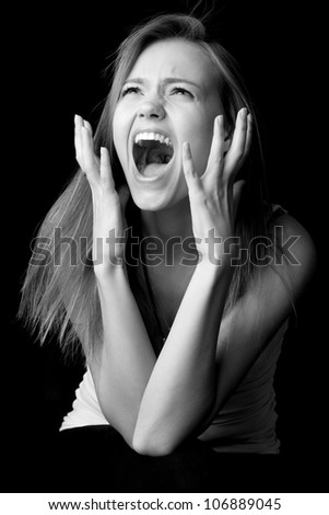 Portrait of screaming girl on black background - stock photo