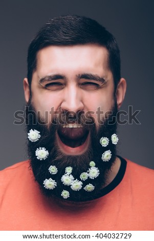 Portrait of screaming young bearded hipster man with flowers in his beard standing against grey background