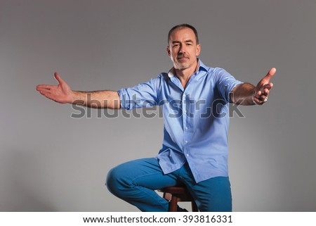 portrait of seated casual man welcoming with open arms while looking at the camera in gray studio background - stock photo