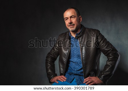 portrait of seated mature man in leather jacket resting hands while looking away from the camera in gray studio background