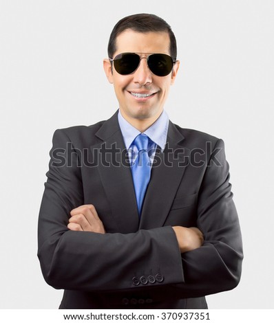 Portrait of secret agent smiling and standing with crossed arms on white background - stock photo
