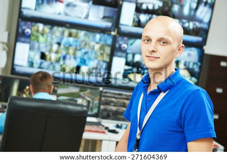 Portrait of security guard over video monitoring surveillance security system - stock photo