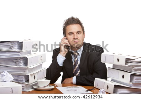 Portrait of self confident businessman which is sitting on his desk full of paperwork, and making a telephone call. Isolated on white. - stock photo