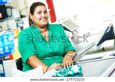 Portrait of seller assistant or cashdesk cashier worker teller in supermarket store - stock photo