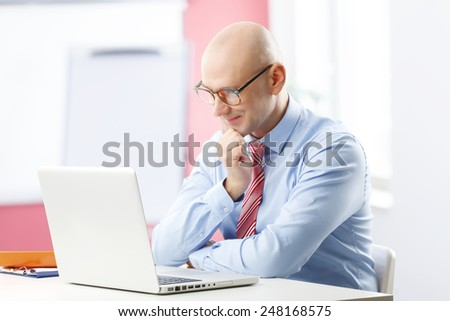 Portrait of senior advisor analyzing data at computer while sitting at office.