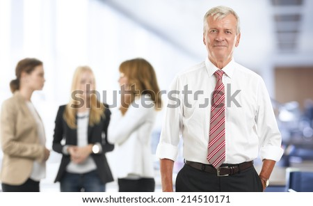 Portrait of senior advisor with colleagues standing at office.  - stock photo