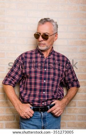 Portrait of senior aged man in glasses on bricks background - stock photo