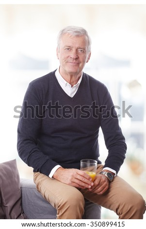 Portrait of senior agency owner sitting at workplace and holding in hand some soft drink while looking at camera and smiling. Small business. - stock photo