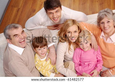 Portrait of senior and young couples and children looking at camera at home - stock photo