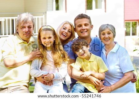 Portrait of senior and young couples with their children looking at camera outdoors by the house - stock photo