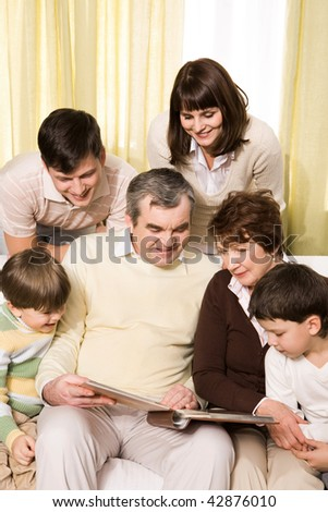 Portrait of senior and young couples with their children looking at family photos