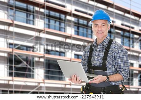 Portrait of senior architect using laptop against building - stock photo