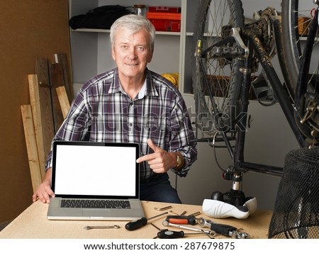 Portrait of senior bike shop owner sitting at desk behind the laptop and points to the white screen of the laptop.  - stock photo
